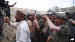 Cư dân giơ những vết thương ra trước các nhà báo địa phương và quốc tế sau khi cảnh sát bắn chỉ thiên để giải tán đám đông gần khu vực sạt lở ở làng Abi Barik, ngày 6/5/2014.