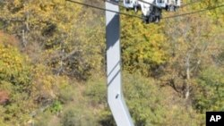 Armenian President Serzh Sarkisian (C) and the head of the Armenian Apostolic Church, Karekin II (L) ride in a cable car at the newly opened cable line near Tatev monastery in Armenia's southern mountains close the border with Iran, 16 Oct 2010