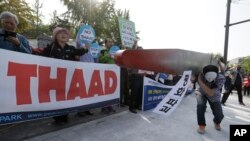 Protesters carry a mock missile symbolizing an advanced U.S. missile defense system called Terminal High-Altitude Area Defense, or THAAD, during a rally to oppose a plan to deploy the THAAD in front of the Defense Ministry in Seoul, South Korea, Oct. 20, 2016.