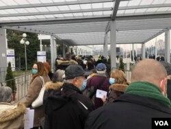 Ljudi čekaju u redu za vakcinaciju i revakcinaciju ispred hale Begradskoj sajma, u Beogradu, 20. februara 2021. (Foto: Jovana Đurović, VoA)