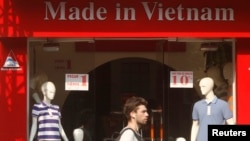A tourist walks past a clothes shop in Hanoi.