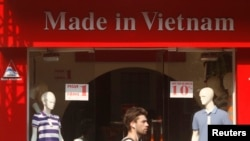 """游客走过河内一家亮出""""越南制造""""字样的服装店。(资料照)"""