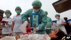 Thành viên Pháp Luân Công diễn lại cảnh thu hoạch nội tạng tại một trại lao động khổ sai ở Trung Quốc, trước Dinh Tổng Thống Đài Loan ở Đài Bắc ngày 23/4/2006.