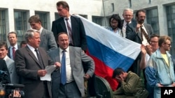"FILE - In this Aug. 19, 1991, photo, Boris Yeltsin, foreground left, at the time president of the Russian constituent republic within the Soviet Union, addresses a crowd standing atop of a tank in front of the ""Russian White House,"" in Moscow, Russia."