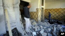 Palestinians inspect the demolished apartment of Abdel Rahman al-Shaludi in east Jerusalem, Israel, Nov. 19, 2014. Israeli authorities demolished the apartment as a punitive measure after al-Shaludi's deadly attack with his car on a Jerusalem train station last month.