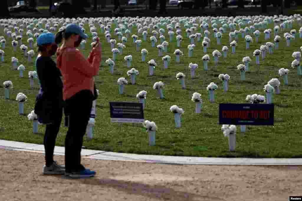Visitors take pictures of the new Gun Violence Memorial, an installation featuring 38,000 silk white roses in 4,000 vases to commemorate the roughly 40,000 Americans who die annually in gun violence, on the National Mall in Washington, D.C.