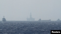 FILE - Ships and an oil rig, center, which China calls Haiyang Shiyou 981, and Vietnam refers to as Hai Duong 981, is seen in the South China Sea, off the shore of Vietnam, May 14, 2014.