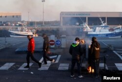 FILE - French fishermen block trucks carrying UK-landed fish to protest for the slow issuance of licenses to fish inside British waters, at the fishing port in Boulogne-sur-Mer, France, Apr. 23, 2021.