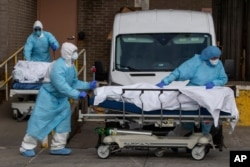 Medical personnel wearing personal protective equipment remove bodies from the Wyckoff Heights Medical Center, April 2, 2020 in the Brooklyn borough of New York.