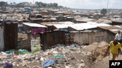FILE - A man walks by the slum of Mathare in Nairobi, May 28, 2014.
