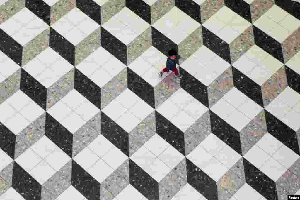 Seorang anak laki-laki berjalan di sebuah mall di Tokyo, Jepang.