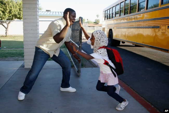 Samuel Lavi, left, a Congolese native who is a teaching assistant and family engagement liaison, greets first grader Kediga Ahmed as she arrives at the Valencia Newcomer School attend class Thursday, Oct. 17, 2019, in Phoenix. (AP Photo/Ross D. Franklin)