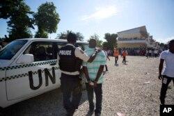 Lapolis arete yon neg yo suspek de frod elektoral nan Potoprens, Ayiti, 25 Oktob 2015.