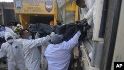 2月15号,洪都拉斯法医工作者往卡车上运尸体。