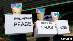 韩国抗议人士戴着用美国、朝鲜和韩国国旗信封做成的面具要求立即举行和平会谈