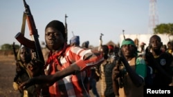 Rebel fighters hold their weapons as they march in a village in the rebel-controlled territory of Upper Nile state, South Sudan, Feb. 9, 2014.