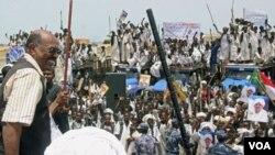 Presiden Sudan Omar Al Bashir (kiri) menyapa para pendukungnya saat mengunjungi kota Osaef (20/6).