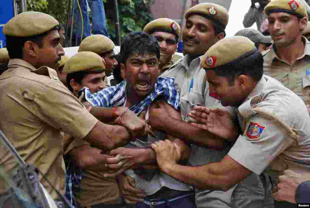 Police detain a supporter of Chandrababu Naidu, chief of Telugu Desam Party (TDP), a regional party, as he tries to stop a vehicle from carrying Naidu to a hospital in New Delhi, India. Naidu was on an indefinite hunger strike since Oct. 7, 2013, against the creation of Telangana state, according to local media.