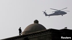 FILE - An Afghan security guard keeps watch on the roof of a building as a NATO helicopter flies overhead in Kabul.