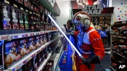 "A fan dressed as a Star Wars character shops at a toy store at the midnight in Hong Kong, Sept. 4, 2015, as part of the global event called ""Force Friday"" to release new toys and other merchandise of the new movie ""Star Wars: The Force Awakens."""