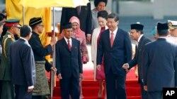 Presiden China Xi Jinping (tengah kanan) dan istrinya Peng Liyuan disambut Raja Malaysia Abdul Halim Mu'adzam Shah (tengah kiri) dan Ratu Haminah Hamidun dengan upacara penyambutan tamu negara di halaman gedung parlemen di Kuala Lumpur, Malaysia (4/10).