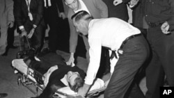 Lee Harvey Oswald, accused assassin of President John F. Kennedy, is placed on a stretcher after being shot in the stomach in Dallas, Texas, November 24, 1963.