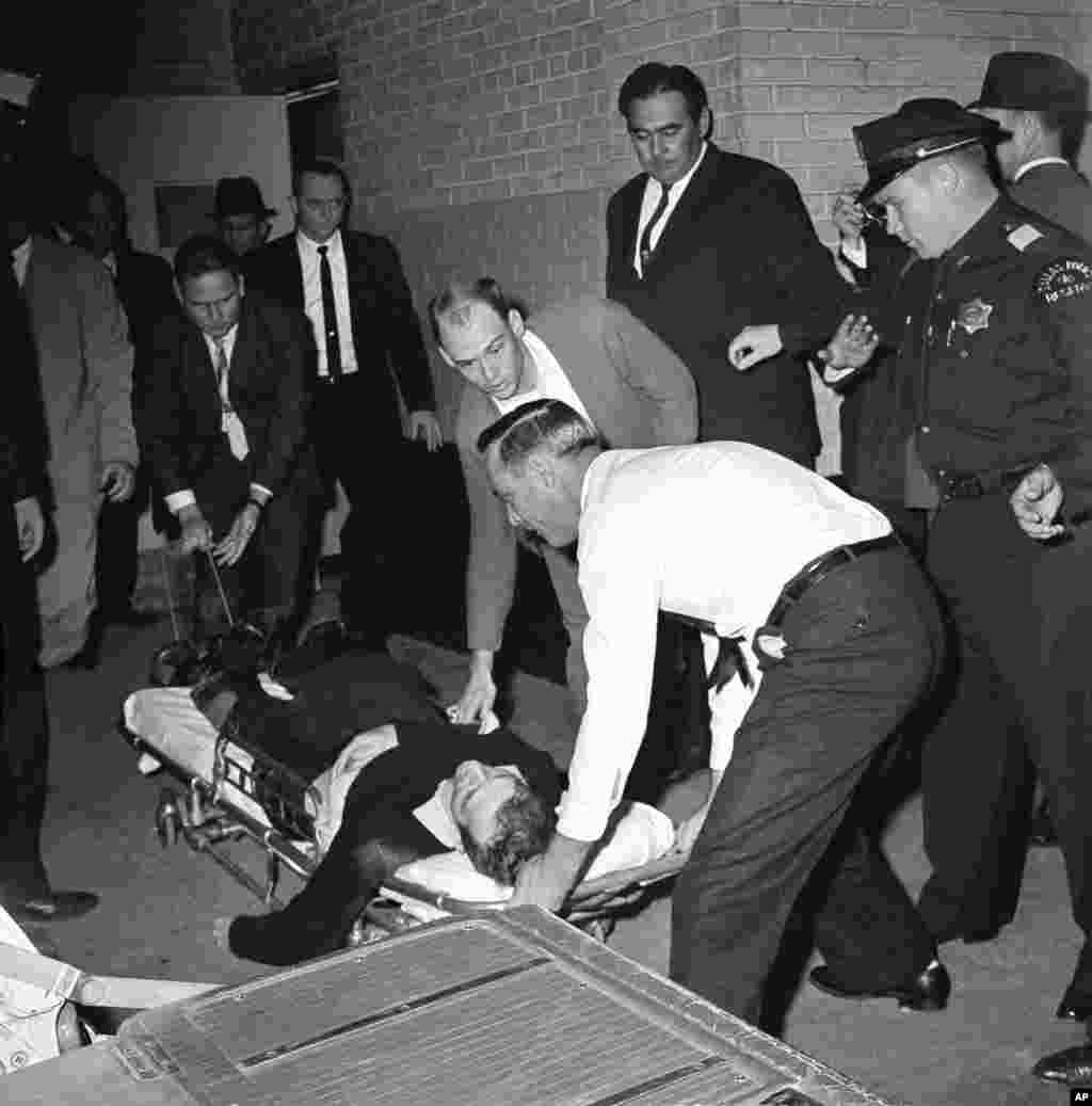 Lee Harvey Oswald, acusado del asesinato de John F. Kennedy, es colocado en una camilla después de recibir un tiro en el estómago cuando era trasladado.