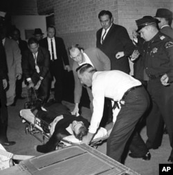 FILE - Lee Harvey Oswald, accused assassin of President John F. Kennedy, is placed on a stretcher after being shot in the stomach in Dallas, Texas, Nov. 24, 1963.