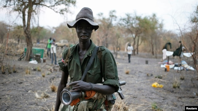 A rebel fighter carries a rocket-propelled grenade (RPG) in a rebel camp in Jonglei state.