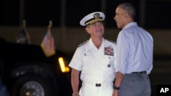 President Barack Obama, right, is greeted by Commander of the U.S. Pacific Command Adm. Harry Harris after arriving at Joint Base Pearl Harbor-Hickam, in Honolulu, Hawaii, Dec. 19, 2015.