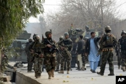 Uniformed and plainclothed Afghan security forces patrol the site of a deadly suicide attack in Jalalabad, Afghanistan, Jan. 24, 2018.
