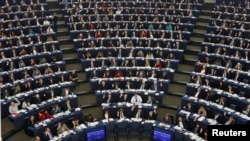 FILE - Lawmakers are seen during a voting session at the European Parliament in Strasbourg, France, Dec. 17, 2014.