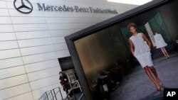 A designer's runway show is shown on a television screen outside the Fashion Week venue at New York's Lincoln Center, Feb. 6, 2013.