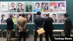 People stand in front of posters showing candidates for the presidential election in Seoul, South Korea