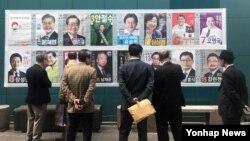 한국 제19대 대통령 선거를 15일 앞두고 서울 중구에서 유권자들이 선거 벽보를 보고 있다.