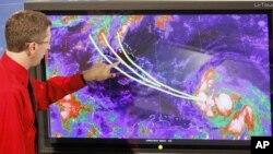 Директорот на националниот центар за урагани Рик Наб ги покажува можните патеки на Исак