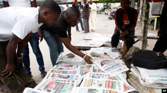 FILE - Men read newspapers with headlines about the Ebola Virus in Lagos, Nigeria.