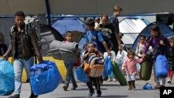 Para migran membawa barang-barang mereka memasuki kota pelabuhan Piraeus, Yunani (7/4).