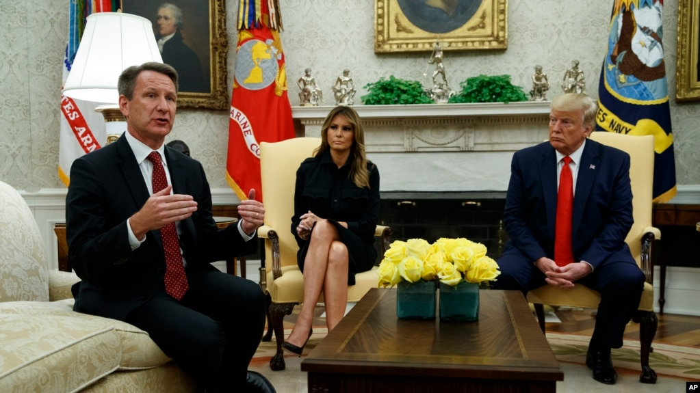 President Donald Trump and first lady Melania Trump listen as acting FDA Commissioner Ned Sharpless talks about a plan to ban most flavored e-cigarettes, in the Oval Office of the White House, Wednesday, Sept. 11, 2019, in Washington. (AP Photo/Evan Vucci