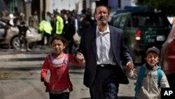 Seorang pria Afghanistan membawa anak-anaknya pergi dari tempat bom bunuh diri yang menyerang konvoi NATO di Kabul, Afghanistan (16/5). (AP/Anja Niedringhaus)