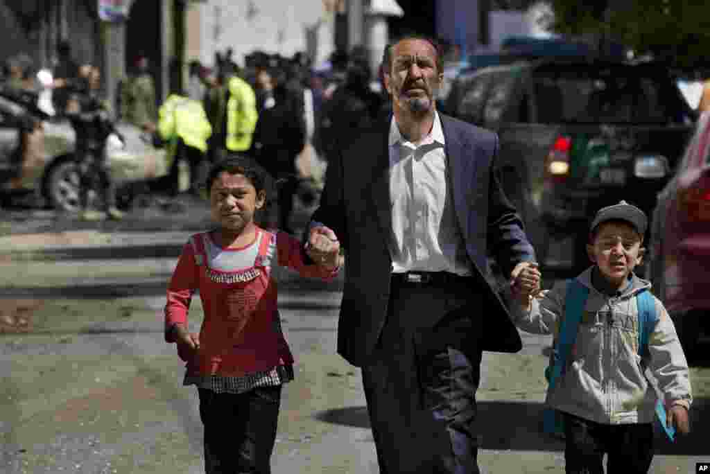 An Afghan man directs his children away from the scene where a suicide car bomber attacked a NATO convoy in Kabul, Afghanistan, May 16, 2013.