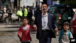 지난해 5월 아프가니스탄의 무장단체인 헤즈브-에-이슬라미가 카불에서 NATO호송대를 목표로 폭탄 테러를 저지른 가운데, 한 남성이 자신의 아이들을 데리고 현장에서 피신하고 있다.