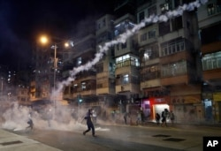 Protesters react to tear gas from Shum Shui Po police station in Hong Kong, Aug. 14, 2019.