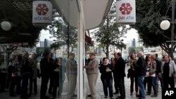 Warga Siprus antri di sebuah ATM di luar kantor cabang bank Laiki di Nicosia, Siprus (21/3). Bank-bank di Siprus masih tutup pekan ini untuk mencegah para nasabah yang panik menarik tabungan mereka.