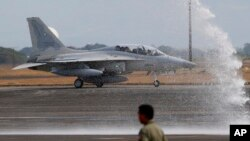 One of two newly acquired FA-50PH fighter jets is given a water cannon salute while taxiing on the runway at Clark Air Base, Philippines, Nov. 28, 2015.