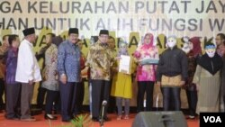 Gubernur Jawa Timur Soekarwo dan Walikota Surabaya Tri Rismaharini, mendampingi Menteri Sosial Salim Segaf Al Jufri, memberikan bantuan Buku Tabungan Secara Simbolis kepada PSK dan Mucikari Dolly dan Jarak di Surabaya, 19 Juni 2014 (Foto:VOA/Petrus)