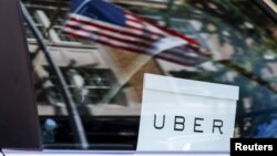 FILE - An Uber sign is seen in a car in New York.