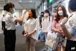 Passengers flying from Busan, South Korea, receive temperature checks for MERS (Middle East Respiratory Syndrome) as they arrive at Hong Kong Airport, June 5, 2015.