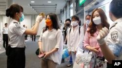 Des passagers arrivant de Busan, en Corée du sud se font prendre la température lors de leur arrivée à l'aéroport de Hong Kong Airport, le 5 juin 2015.