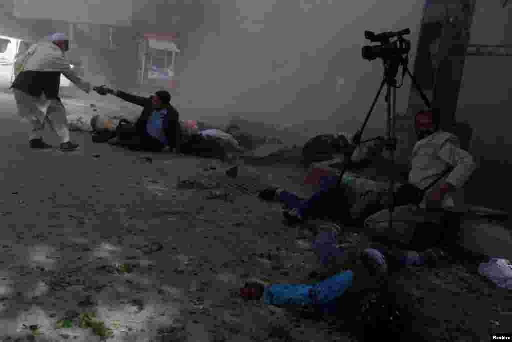 Afghan journalists are seen after a second blast in Kabul.